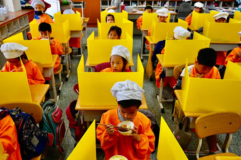 Kinderen eten hun middagmaal aan hun met plastic schotten afgeschermde lessenaars op een basisschool in Taipei. De Taiwanese bestrijding van de covid-19-epidemie is tot nu toe zeer succesvol.  Beeld Sam Yeh / AFP