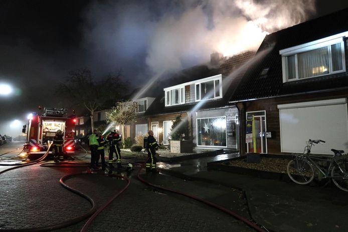 De brand woedt aan de achterzijde van de woning.