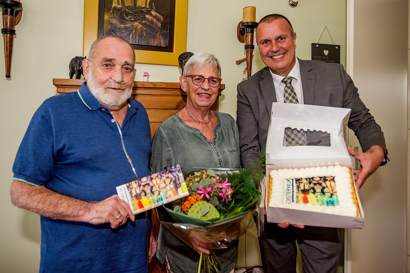 Wethouder Dion Dankers overhandigt - met taart - het echtpaar Potters het mantelzorgcompliment van Oisterwijk: twee bonnen van 12,50 euro.