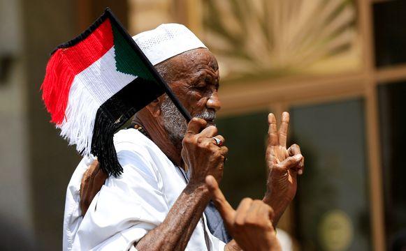 Een man draagt een Sudanees vlaggetje en maakt het vredesteken.