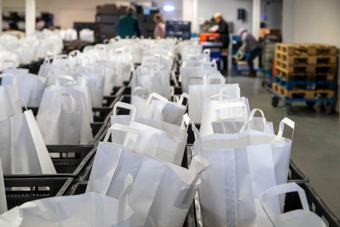 Vrijwilligers pakken voedselpakketten in in het pand van Voedselbank Neder Veluwe aan de Industrieweg in Wageningen. Om de kans op besmetting met het coronavirus zo klein mogelijk te houden, gebeurt dat nu in papieren zakken.