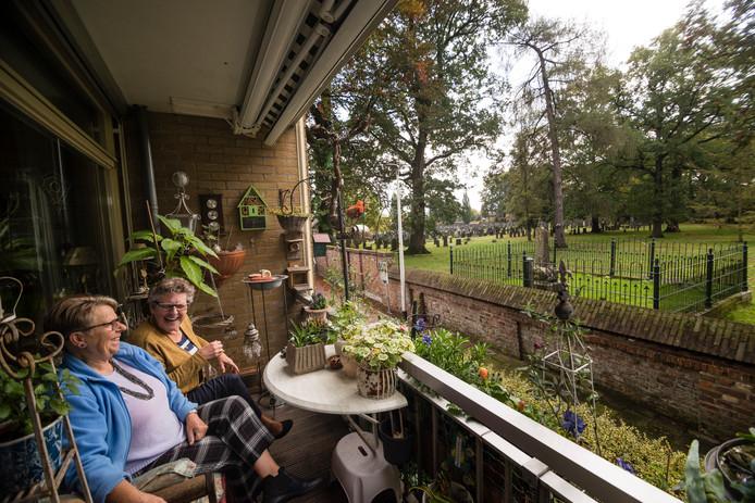 De dames Zwiers en Teela kijken vanaf hun balkon uit over de oude begraafplaats aan het Lentfersweg in Rijssen.
