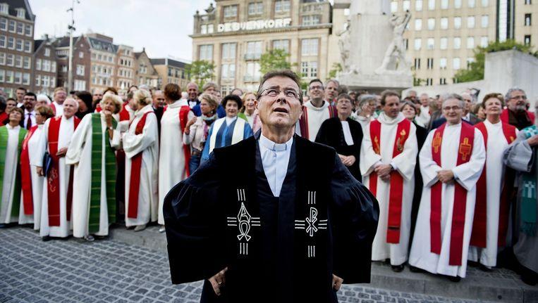 Dominees en kerkelijke werkers op de Dam in Amsterdam tijdens de landelijke predikantendag van de Protestantse kerk. Beeld anp