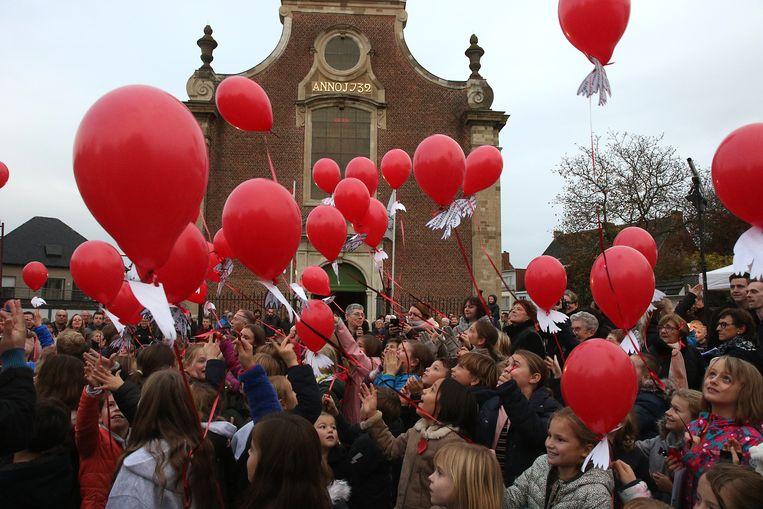 Kinderen lieten rode ballonnen met vredeswensen op.