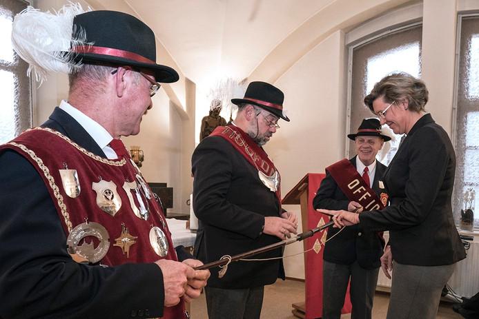 Burgemeester Jobke Vonk-Vedder krijgt van hoofdman Adrie van Straaten uitleg over de kruisboog.