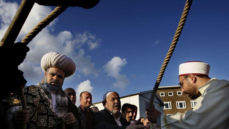 Een imam (R) overhandigt in 2008 tijdens een feestelijke plechtigheid op het terrein van de nog te bouwen Westermoskee in het Amsterdamse stadsdeel De Baarsjes een touw waarmee op symbolische wijze de eerste paal van de moskee kan worden geslagen. Beeld ANP