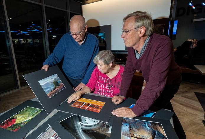 Fotografen Harrie Rijven (l), Dirk Staut en Janine Pompe komen wekelijks samen om over hun foto's te praten.