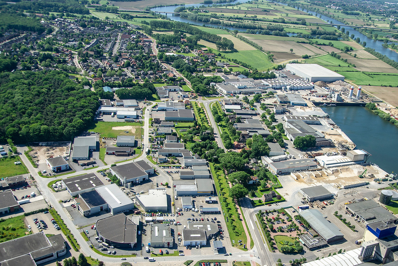 Industrieterrein Hoogveld en de haven vanuit de lucht, met het dorp Heijen op de achtergrond.