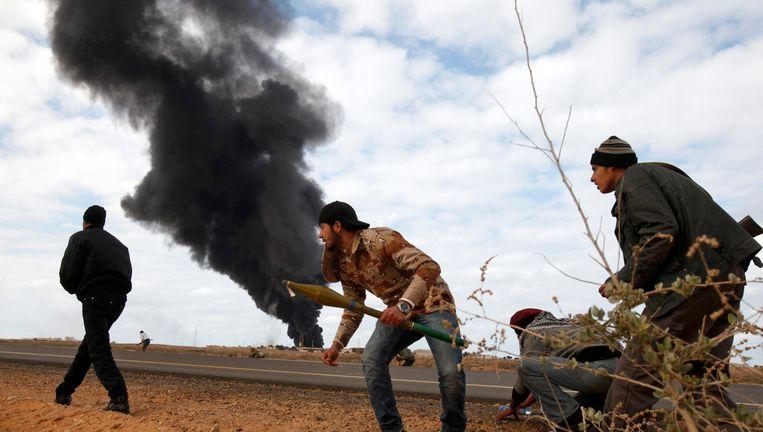 Op de achtergrond de rook na een bombardement van Kadhafi's troepen, op de voorgrond opstandelingen. De foto is vorige week gemaakt tussen Ras Lanuf en Bin Jawad. Beeld reuters