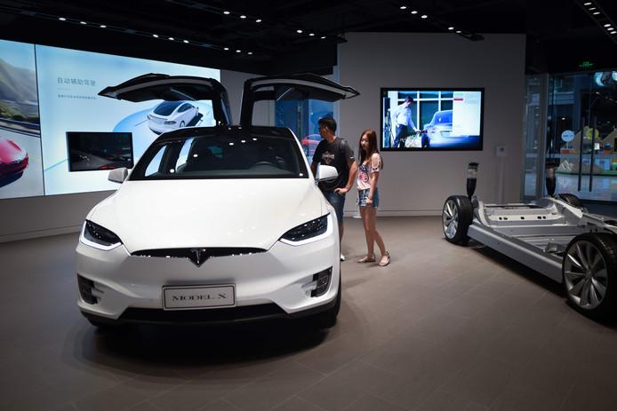 Bezoekers in een showroom van Tesla in China. De milieubewuste Chinees zal veel dieper in de buidel moeten tasten om de Amerikaanse auto te kunnen rijden.