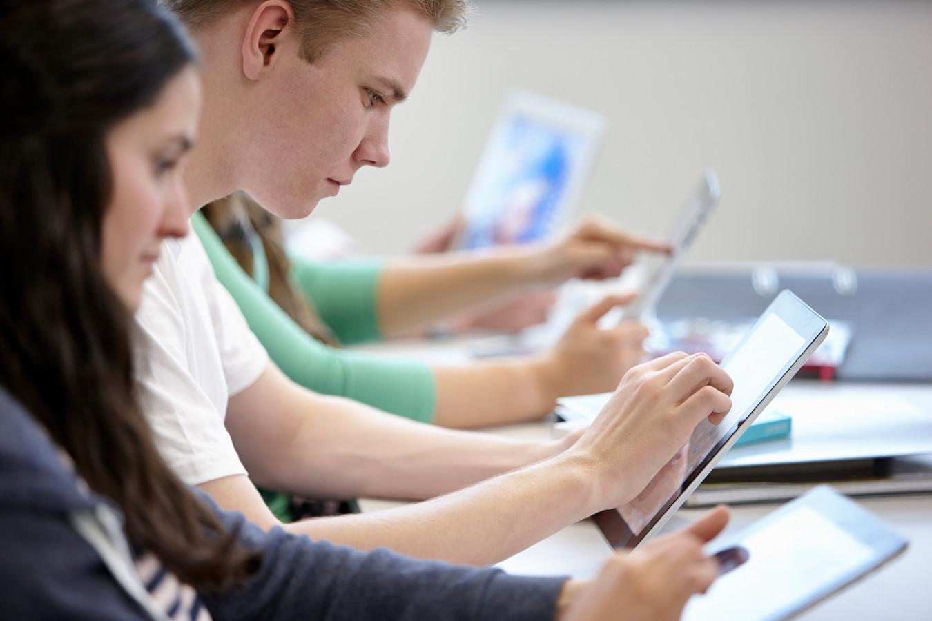 Wie een collegezaal inloopt, ziet vaak geen studenten meer met boeken, pen en papier, maar achter een opengeklapte laptop of met tablet.