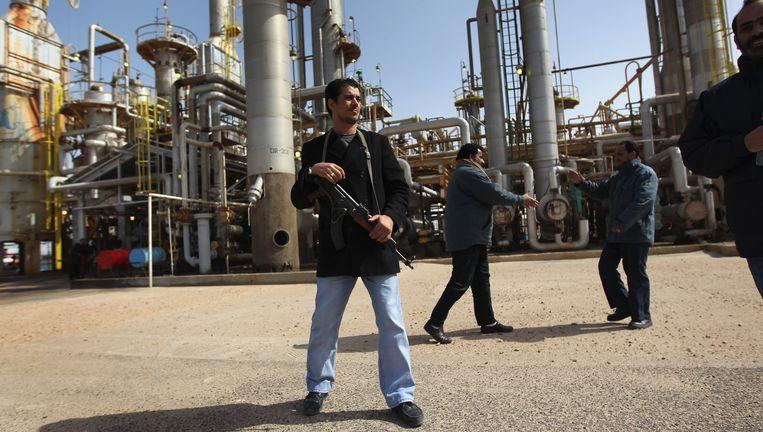 Een anti-Kadhafi-betoger bewaakt een belangrijke olieraffinaderij in Brega. Beeld null