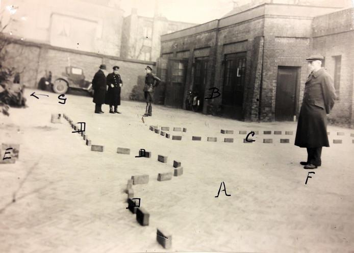 De plaats aan de Willemstraat in Breda waar kunstschilder Frank de Bruijn en arts Willem Jan Scheffelaar zijn geëxecuteerd. Rechts, met het petje, de voormalige Feldwebel Wiegand, de Duitser die de twee mannen heeft neergeschoten. De foto is genomen tijdens een reconstructie van de executie in 1948. De letter E verwijst naar de plaats waar de twee mannen stonden toen ze werden doodgeschoten.