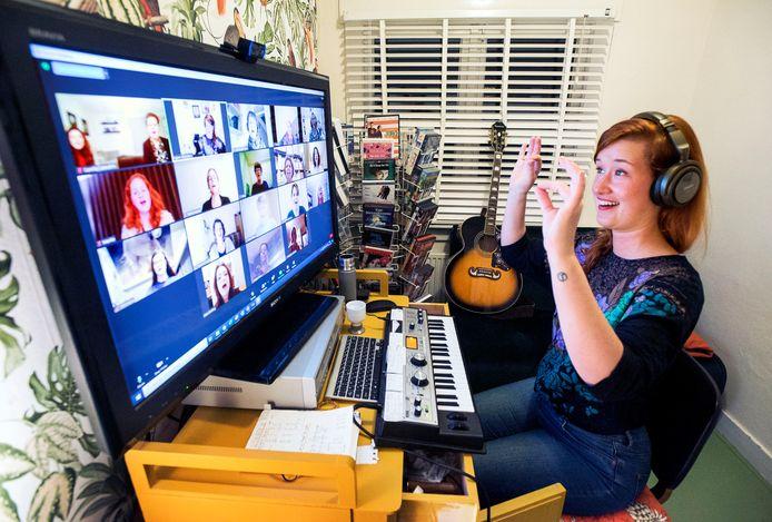 Dirigent van Het Klooster Popkoor uit Woerden Agnes Loonstra begeleidt en dirigeert haar koor vanachter haar computer.