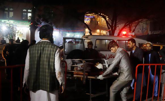 Een gewonde wordt afgevoerd met een ambulance.