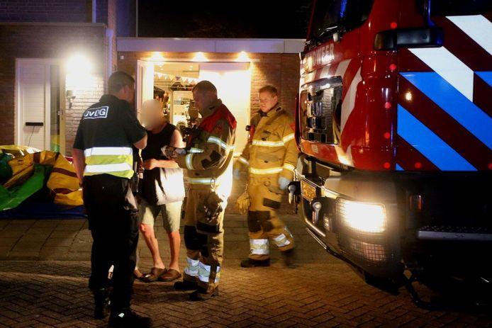De brandweer met de fles bio ethanol waar de brandbare vloeistof in Nieuwkuijk uit kwam.