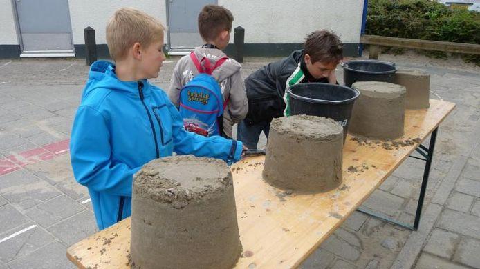 Kinderen mogen met speciaal zand zelf een sculptuur maken op de speelplaats van De Bron.foto Domien van der Meijden/BD