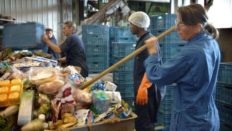Medewerkers van Sita Food Recycling gooien voedsel uit supermarkten, de dranken- en voedingsindustrie in containers (2005). Beeld Marcel van den Bergh / de Volkskrant