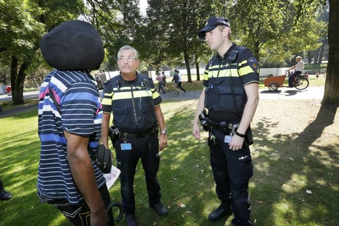 Wijkagent Henk Woestenberg en politieman Bas van der Moezel (r), projectleider aanpak Slingerweg, in gesprek met ' Rambo', een van de daklozen in het park. Foto's Joyce van Belkom/Pix4Profs
