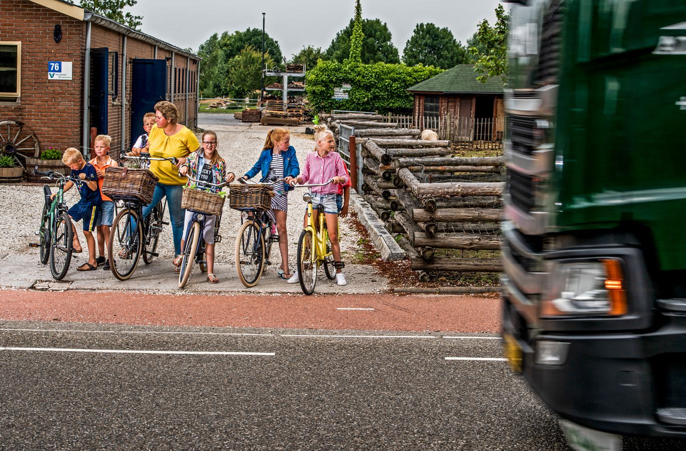 Marielle Verbakel met de kinderen op de fiets terwijl zij de Halve Raak op wil rijden. De provincie wil er een provinciale weg van maken. Foto: Frank de Roo