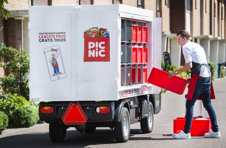 Een medewerker van de online supermarkt Picnic bezorgt boodschappen bij een klant met een elektrische bezorgtruck.  Beeld anp
