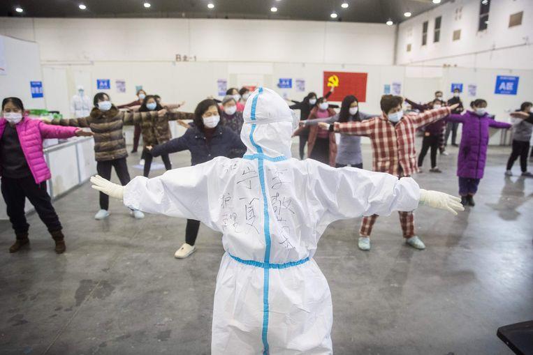 Een groep patiënten met lichte symptomen krijgt een sportles in Wuhan. Beeld AFP