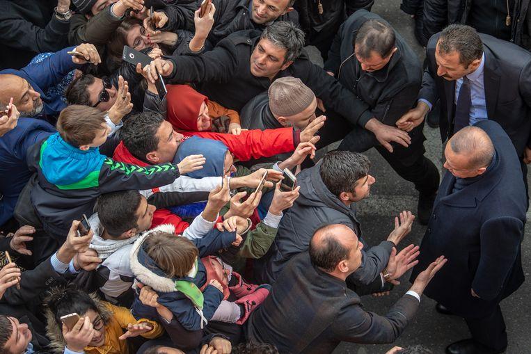 De Turkse president Recep Tayyip Erdogan (rechts) in gesprek met burgers, bij de lokale verkiezingen in Istanbul in maart van dit jaar.  Beeld AFP
