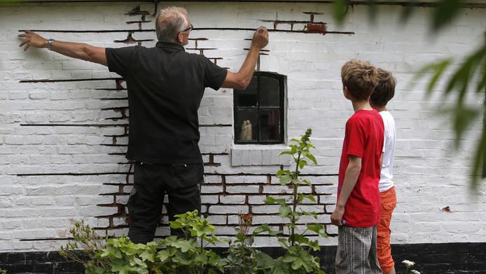 Een inwoner van Loppersum plaatst ijzeren pennen in zijn woning na een aardbeving in het noorden van de provincie Groningen.
