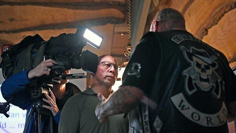 No Surrender-voorman Henk K. eerder dit jaar op een persconferentie in gesprek met een tv-journalist naar aanleiding van de aantijgingen van het Openbaar Ministerie dat de motorclub achter de bedreigingen zou zitten van de locoburgemeester van Emmen. Beeld Guus Dubbelman / de Volkskrant