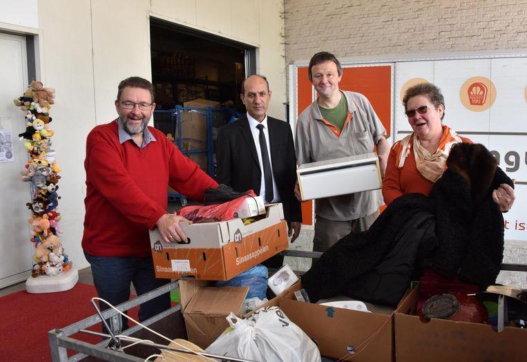 André Van Bourgognie en Paula Verbeek brengen spullen tot bij ceremoniemeester Majid en medewerker Koen Goris.