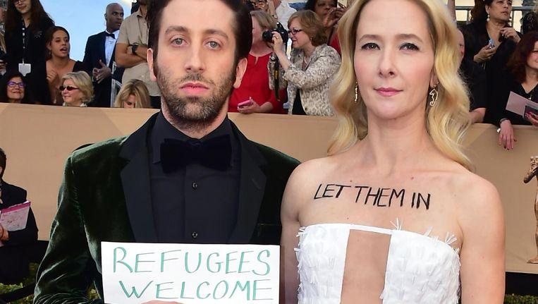The Big Bang Theory-acteur Simon Helberg op de rode loper met een bordje met de tekst 'refugees welcome'. Zijn echtgenote actrice Jocelyn Towne schreef 'Let them in' op haar borst Beeld afp