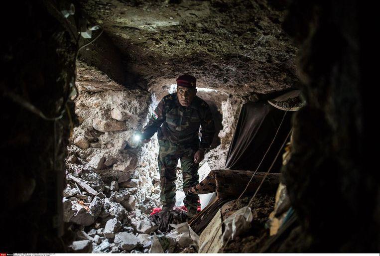 Een peshmergastrijder inspecteert in Sinjar een door IS aangelegde tunnel met slaapruimten. De tunnels onder de stad zitten ook vol boobytraps. Beeld Laurence Geai/Hollandse Hoogte
