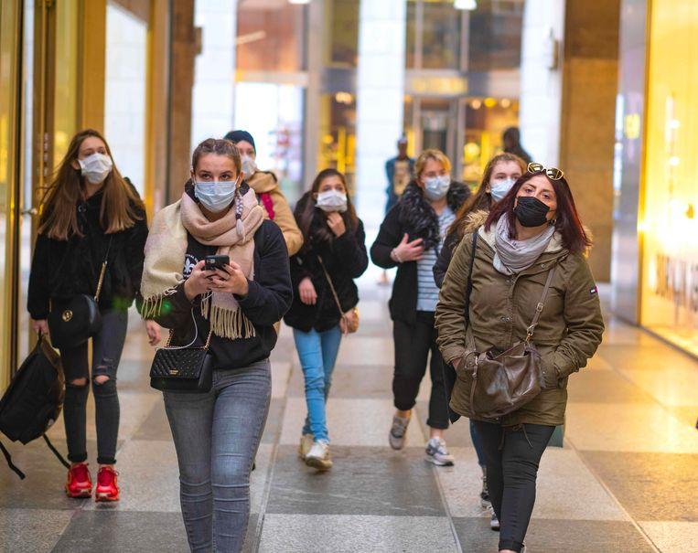 Shoppen in de Italiaanse stad Milaan, tegenwoordig doen verschillende mensen het met een mondmasker. De vrees voor het nieuwe coronavirus zit er goed in.