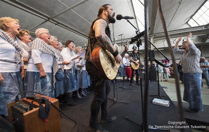 De afscheidsmaaltijd burgemeester Jon Hermans in oude fabriekshal van Ten Cate op Indieterrein. Er zitten 800 mensen aan tafel en er zijn meerdere optredens, met verrassende combinaties, zoals De Schellevissen en de Bottleneck rockers.