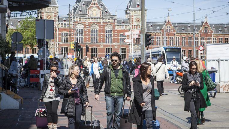 Bezoekers aan Amsterdam met rolkoffers op de kop van het Damrak. Het geluid van de wieltjes is het nieuwe kenmerkende geluid van Amsterdam, stelt Lein Bakker Emmelot. Beeld Floris Lok