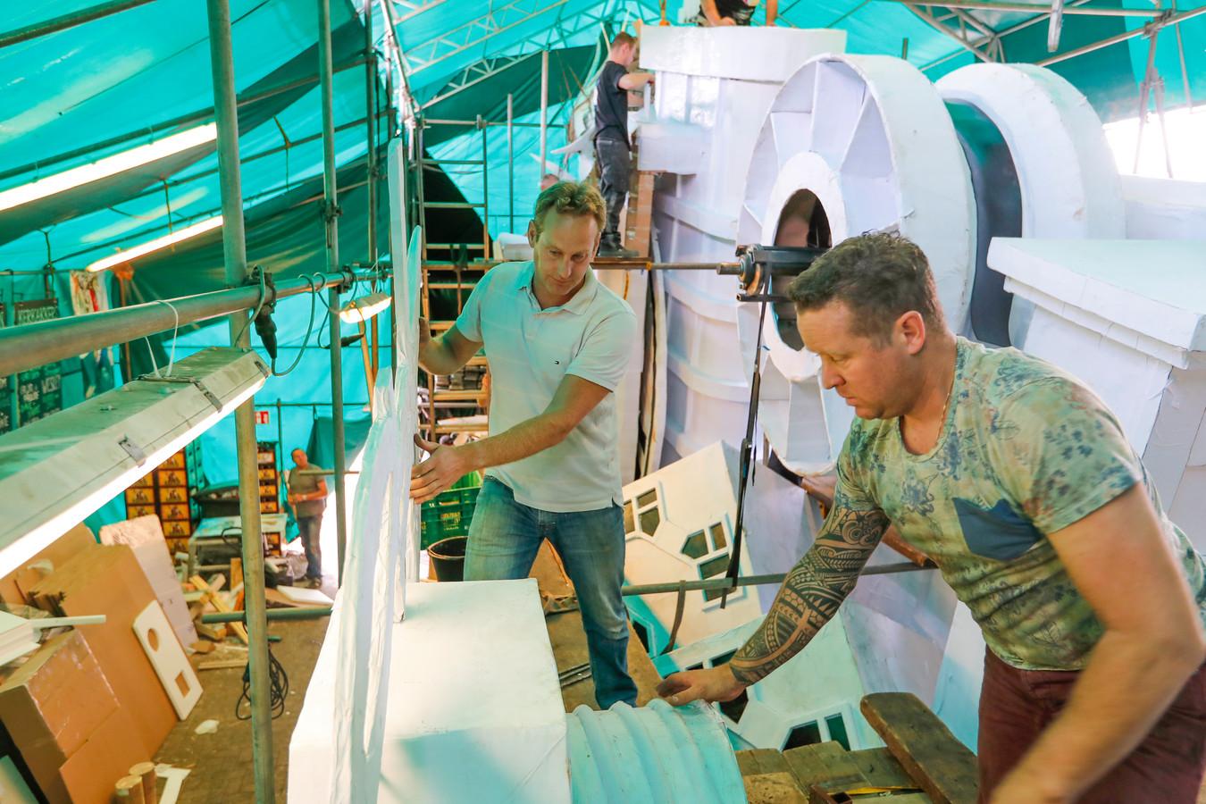 Dave Schaeken (l) en Edwin van der Heijden werken aan hun corsowagen.
