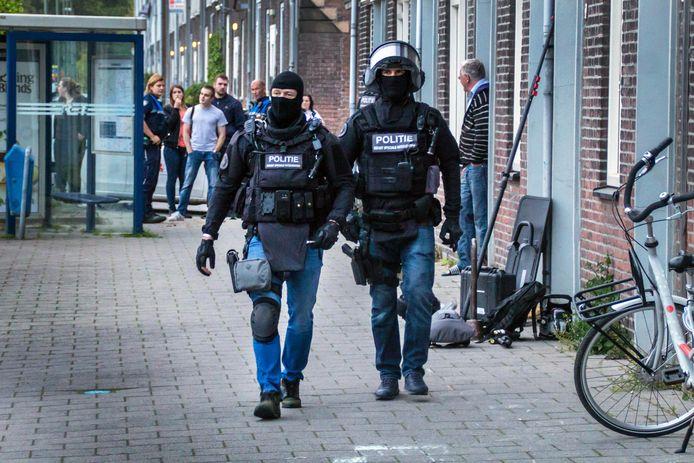 Zwaarbewapende agenten lopen in de Vlaardingse Parallelweg.