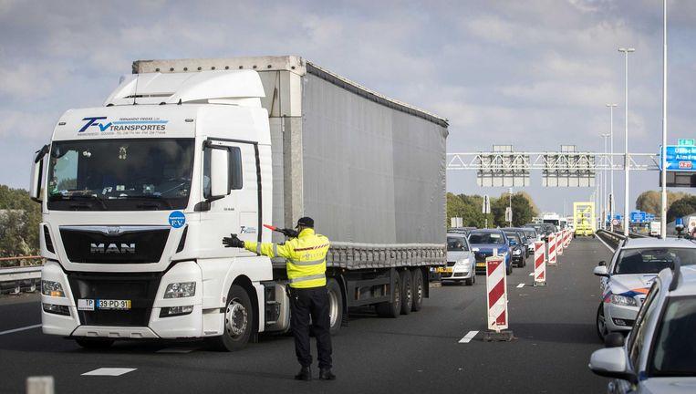 Een politieman dirigeert een buitenlandse vrachtwagen op de A27 naar de afrit van Avelingen, vanuit noordelijke richting de laatste voor de Merwedebrug. Beeld null