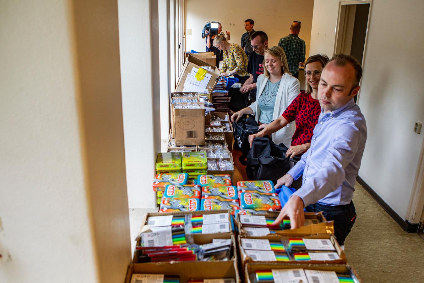 Ambtenaren van de gemeente hielpen vandaag met het inpakken van de pakketten. Rechts wethouder Rob de Geest (PvdA).