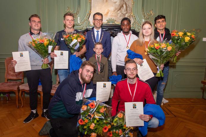 De acht aanwezige jongeren te midden van wethouder Derk Alssema. Achterste rij van links naar rechts: Danny Jansen, Werner Verhaegen, Glori Matondo, Eva Konings, Yassine Azzagari. In het midden: Liam Kruijt. Op de voorgrond: Tim Snoep (links) en   Luc Beukering.