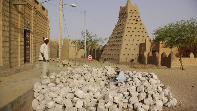 Straatwerkers nabij een moskee in de typische bouwstijl van van Timboektoe