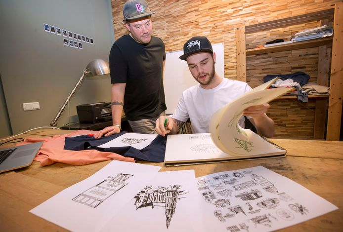 Billy Zomerdijk (links) en tekenaar Steef van Loenhout met de ontwerpen voor hun T-shirts en hoodies.