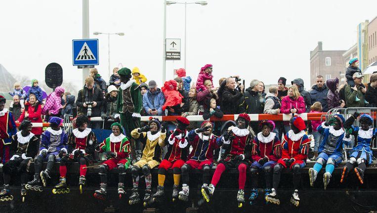 Een groep Zwarte Pieten (roetpieten of schoorsteenpieten) met slechts enkele roetvegen op het gezicht en op rolschaatsen wacht op de komst van Sinterklaas tijdens de intocht in Amsterdam. Beeld anp