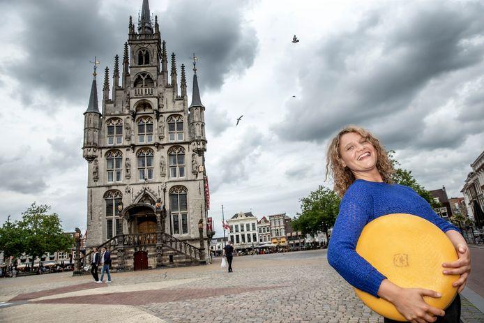 Culinair journalist Laura de Grave op de Markt van Gouda, met Goudse kaas die wél in Nederland wordt gemaakt.