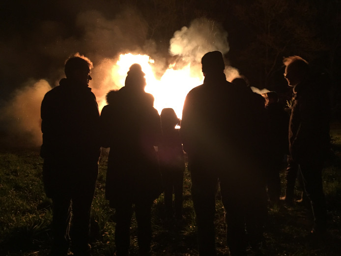 Publiek geniet van de vlammen in de avond tijdens de kerstboomverbranding in Riel.