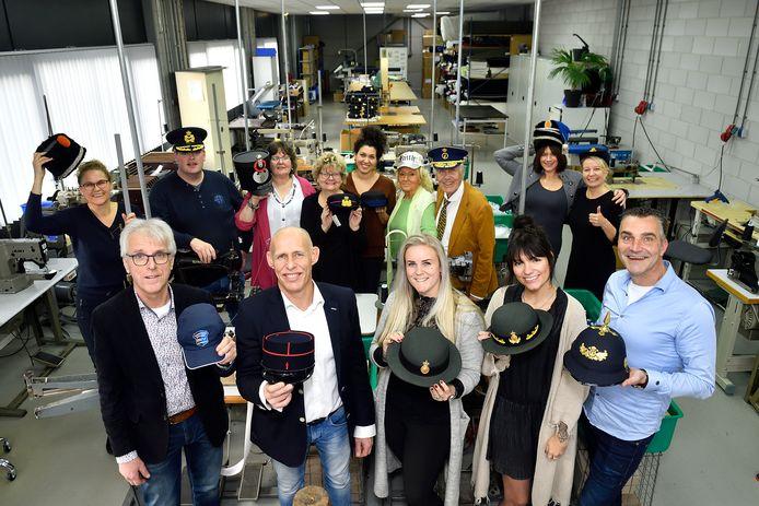 Trots toont het personeel van Hassing samen met eigenaar Albert Have (eerste rij, tweede van links) een greep uit de ruime keuze aan hoofddeksels.