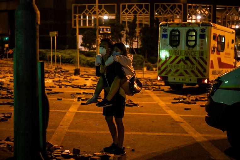 Een jongeman draagt een gewond meisje naar een ambulance aan de Polytechnische Universiteit.