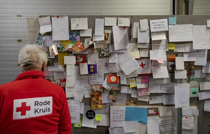 Een vrijwilliger van het Rode Kruis staat voor een wand met hartverwarmende kaartjes van gulle gevers.