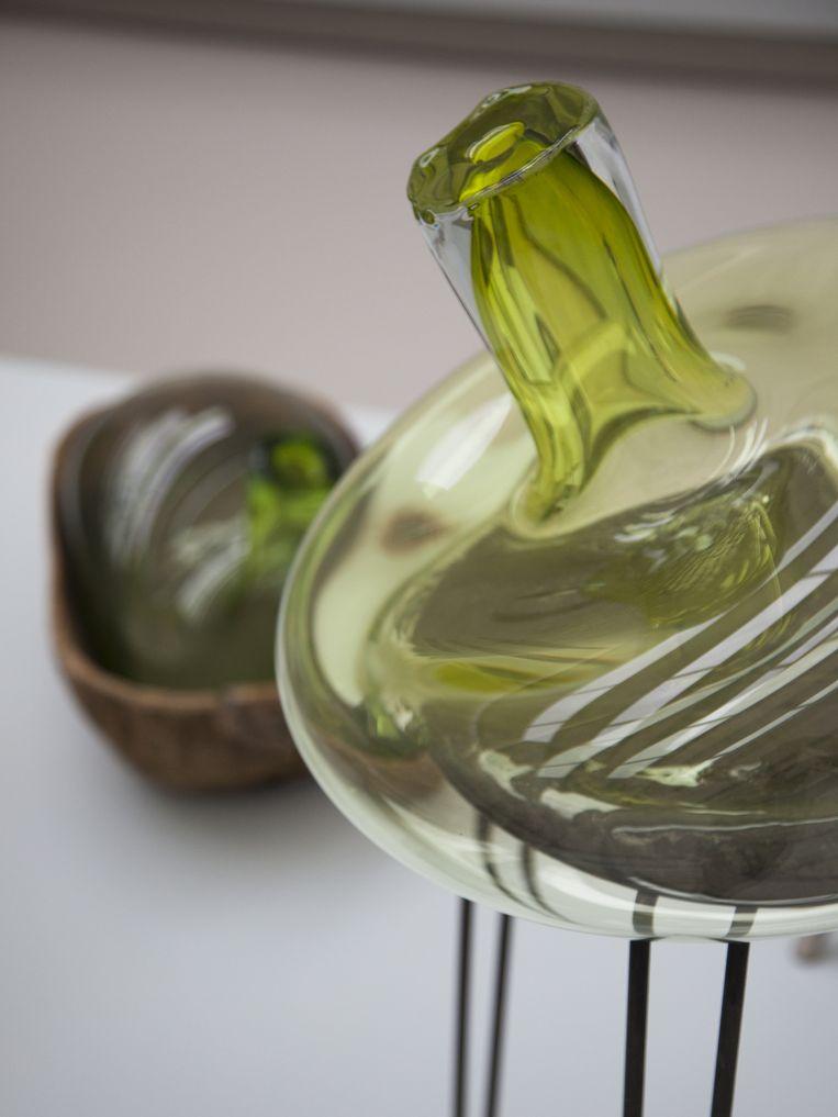 Crystal Virus (2006) is een langlopende serie van vazen die zijn gekoppeld aan een ander object. Soms zakt het geblazen glas uit over een eikenhouten balk, maar ook een stoel van Rietveld of klassieke ontwerpen van Vitra dienen als leunobject voor het glas. Beeld Pieke Bergmans