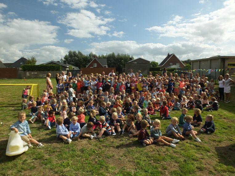 De leerlingen van basisschool Mozaïek op de speelweide achter hun school.